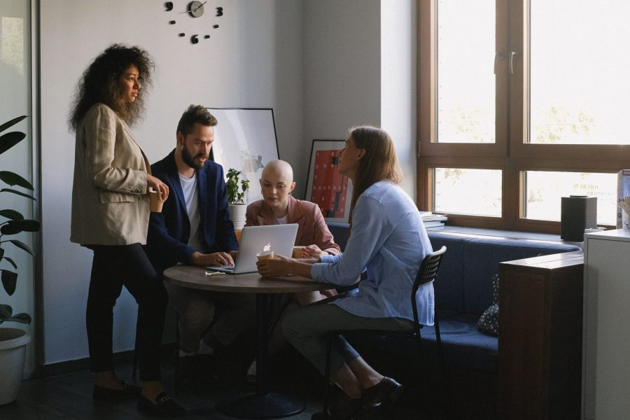Group of diverse colleagues using laptop and talking in office