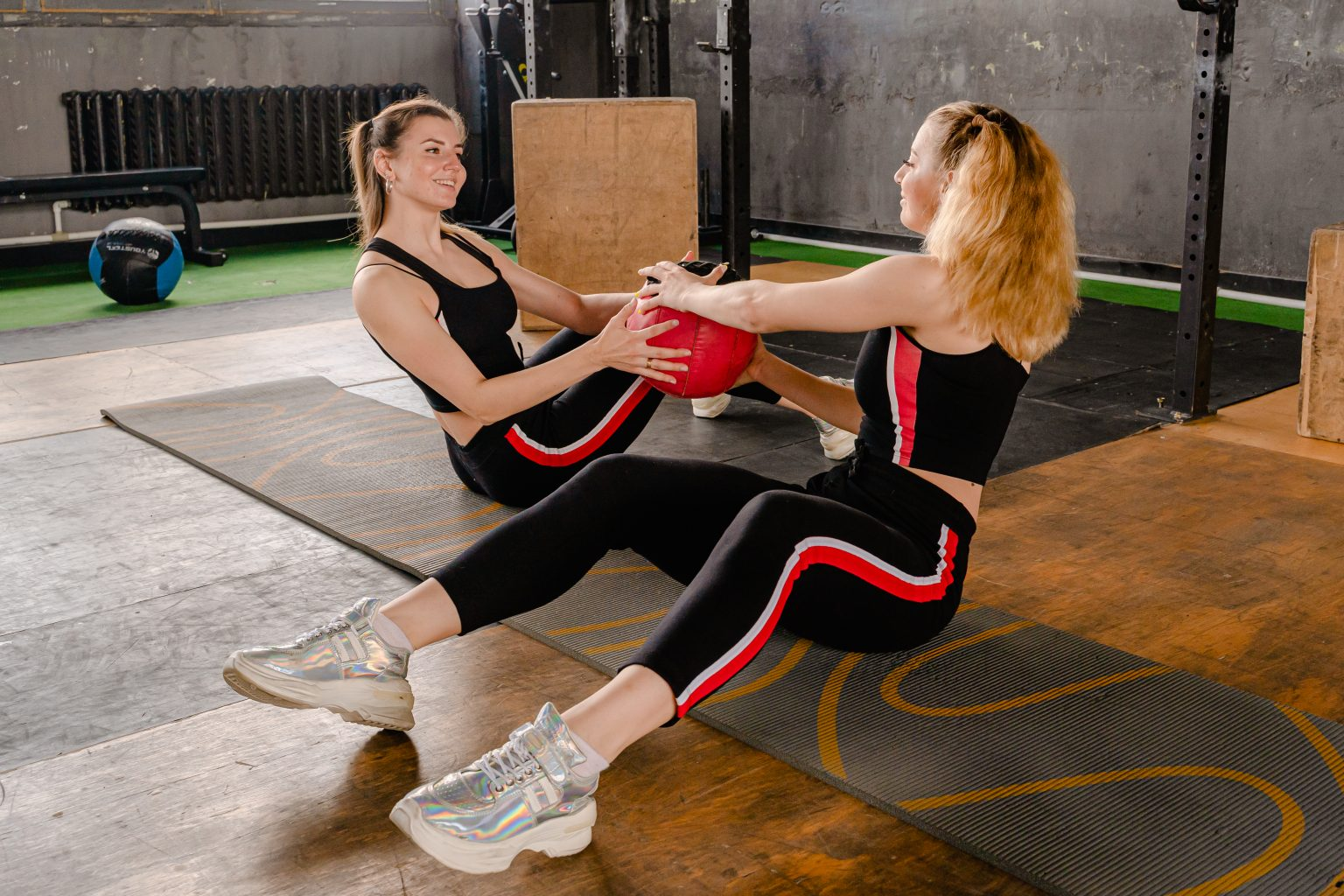 Photo of women sitting on floor while holding an exercise ball